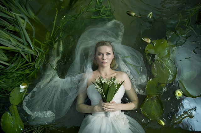 Still from the movie Melancholia. Kirsten Dunst, a young blonde white woman, in a white wedding dress and veil, holding a bouquet of white flowers, floating down a river on her back, surrounded by green reeds and lily pads.