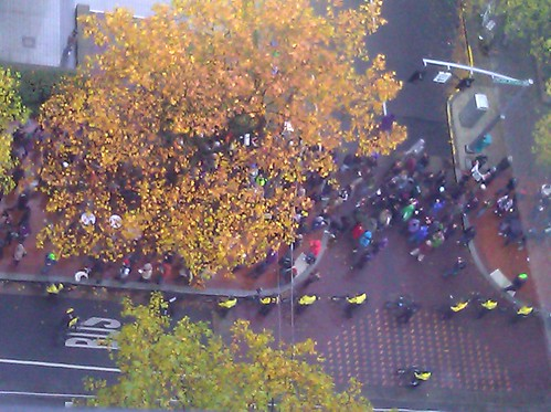 An Occupy march down 5th Avenue in Portland, flanked by neon-vested bike police, seen from the 14th floor of the Portland Building