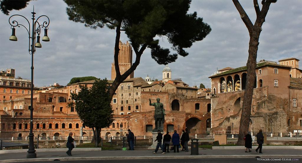 A via dei Fori Imperiali está decorada com estátuas dos grandes dirigentes romanos, como aqui, a estátua de Trajano, de frente para os mercados de Trajano.