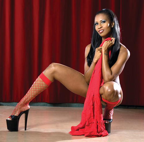 Essence wearing red shoes and accessories, posing on a stage