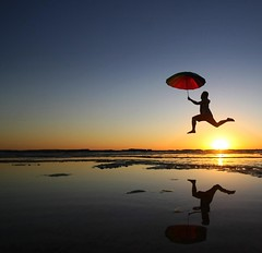 Mr. Poppins (pominoz) Tags: people reflection silhouette umbrella sunrise newcastle jump nsw susangilmorebeach