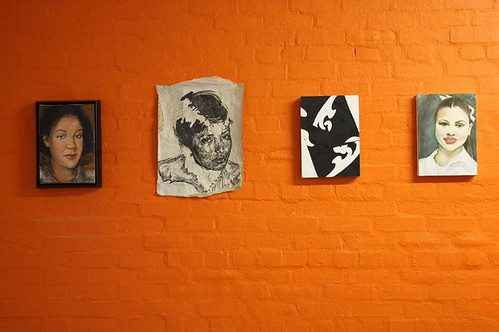 orange gallery wall with four paintings of women hanging on it