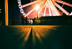 The Big Wheel (fotobes) Tags: film night 35mm lights lomo lca xpro lomography couple candid watching spinning glowing analogue lowdown fujiastia100 leadinglines ratseye chinscraper fotobes brightonwheel