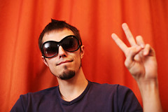 Hip young man showing V sign (EASTCOBBERMagazine) Tags: red portrait people orange white man color male guy face sunglasses fashion sign horizontal pose beard fun goatee photo cool model peace hand adult head expression finger unitedstatesofamerica fingers young posing style funky victory retro dude attitude v trendy 70s casual hip gesture relaxed success carefree oneperson 20s caucasian
