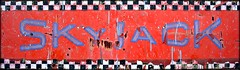 skyjack. (swindlehorne) Tags: blue red sky white black work logo jack outside words rust paint lift letters platform scratches device aerial weathered drips aged checkers trademark brand checkerboard corrosion scuffs skyjack