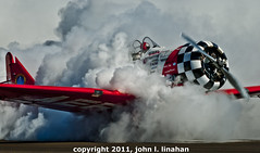 Smoke Out (Jobe Roco) Tags: red plane airplane nikon louisiana lafayette smoke checkerboard t6 aerobatics 2011 sigma135400mm 4217 d80 teamaeroshell sertomacajunairfestival lafayetteairport americantexan