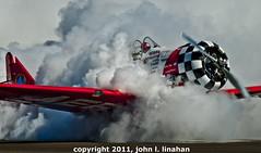 Smoke Out (Jobe Roco) Tags: red plane airplane nikon louisiana lafayette smoke checkerboard t6 aerobatics 2011 sigma135400mm 4217 d80 teamaeroshell sertomacajunairfestival lafayetteairport americantexan