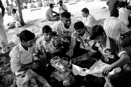 While waiting for their bus, a group of Indian workers regaled tales of the day and inspect their day's purchases.