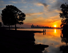 last catch - Detroit River sunset (Wade Bryant) Tags: city light sunset sky color tree silhouette skyline clouds reflections fishing neon detroit belle riverfront isle generalmotors nikond300 nikon1685mmf3556