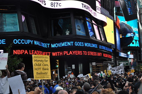 A headline for Occupy Wall Street flashes above the crowd.