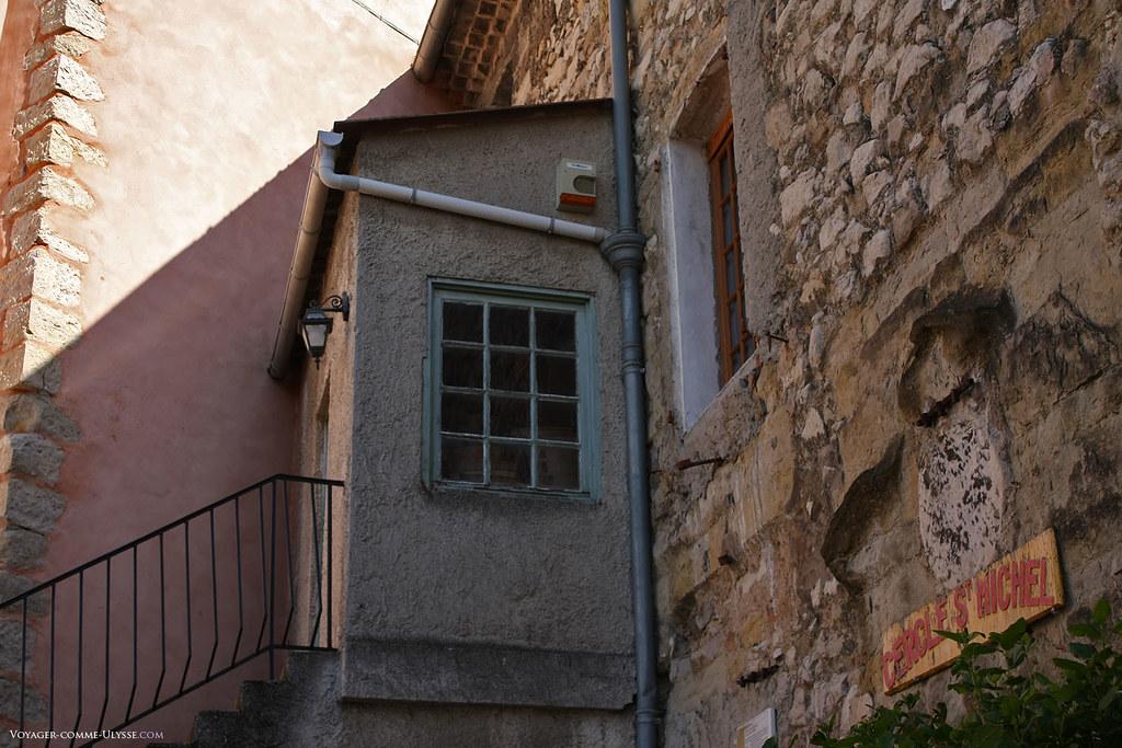 Escalier extérieur pour accéder à l'étage. On observe la fenêtre à carreaux, presque aussi grande que le mur.