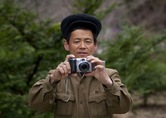North korean man taking a picture of me - North Korea (Eric Lafforgue) Tags: camera people man color colour male hat horizontal person concentration war asia korea communism cap casquette asie coree personne couleur humanbeing communisme homme northkorea takingapicture dprk coreadelnorte appareilphoto nordkorea colorpicture waistup 7080 democraticpeoplesrepublicofkorea  couvrechef   coreadelnord  prendreunephoto etrehumain coreedunord  insidenorthkorea  rpdc  kimjongun coreiadonorte  republiquepopulairedemocratiquedecoree cadragealataille