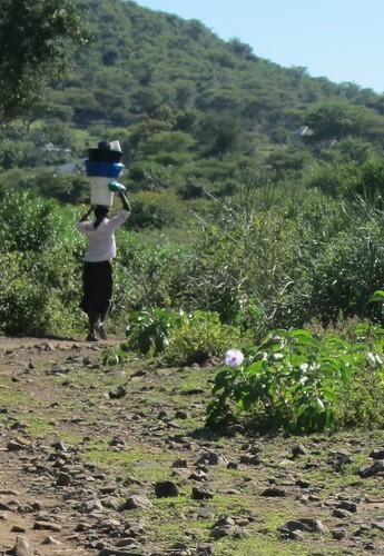 woman carrying dishes on head Mbita kenya by Danalynn C