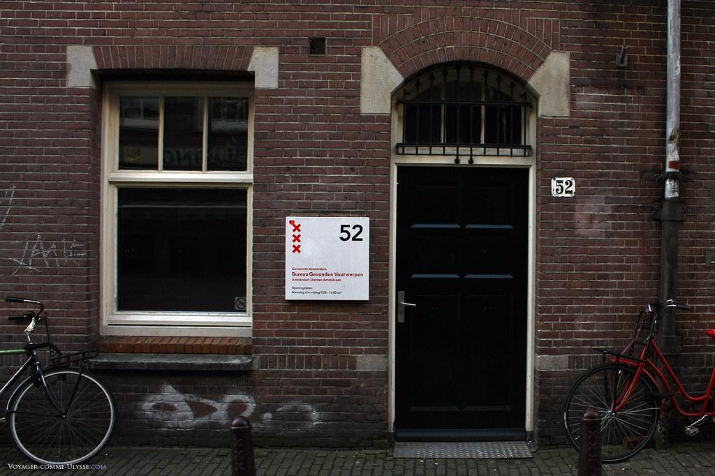 Porte d'entrée d'un immeuble de briques, appartenant à la municipalité.
