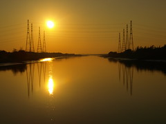 Preston Sunset over the River Ribble (Tony Worrall Foto) Tags: uk sunset england sun reflection wet water lines electric river photo power northwest image north stock scenic sunny estuary preston serene sunlit pylons banks ribble prestondocks prestonian 2011tonyworrall