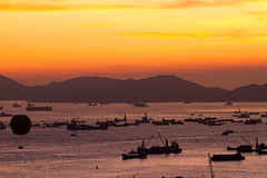 Fragrant Harbour: Sunset (tamjty) Tags: china city light sunset red sky urban orange sun mountains canon landscape boats hongkong eos is asia glow colours harbour balloon silhouettes 7d f28 barges 70200mm