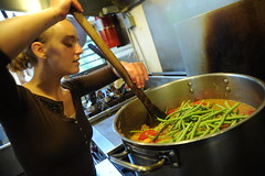 Making vegetarian green bean soup, cook, young woman in a brown shirt, pot, kitchen, Breitenbush Hot Springs, Breitenbush, Oregon, USA