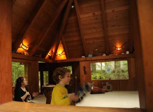 Mother and son playing music and dancing in the activities center, warm wood, hot water heated, Breitenbush Hot Springs, Breitenbush, Marion County, Oregon, USA by Wonderlane