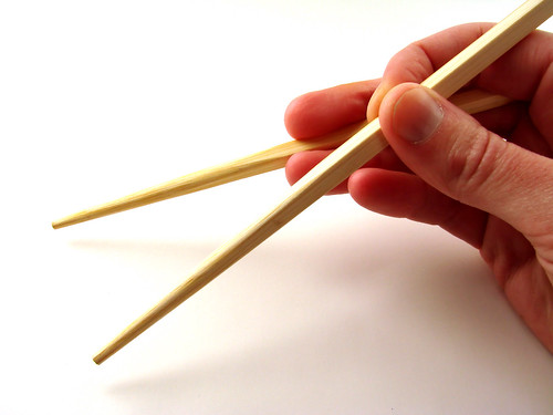 A hand holding a pair of chopsticks