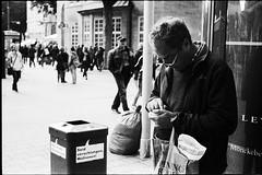 Verschlungen (anauhu) Tags: street people hamburg candid portrait glasses bin cash money blackandwhite bw sw analog film leica m6 ttl hp5 rodinal 50mm elmar grain speechbubble