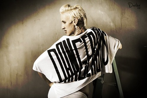 A photograph of Dylan Ryan, a white queer woman with short, bleached blonde hair. She is photographed from the side, wearing a large, flowing shirt that reads DANGEROUS