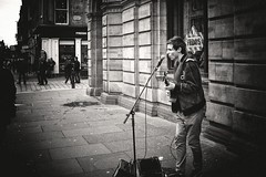 Pass Me By (Explored) (stephen cosh) Tags: life street city people blackandwhite bw musician sepia mono scotland town unitedkingdom glasgow candid streetphotography rangefinder singer fujifilm busker reallife humancondition x100 blackandwhitephotos blackwhitephotos stephencosh fujix100