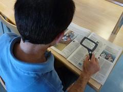 Un usuario lee cómodamente en la biblioteca municipal de Ermua con ayuda de una lupa de sobremesa