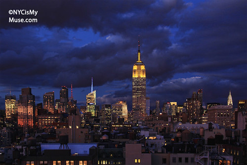 Empire State Building dressed all in yellow in a massive cloud covered twilight sky