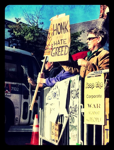 Occupy Northampton: people standing along a street holding protest signs reading Stop the Corporate War Against the People and Honk if You Hate Greed