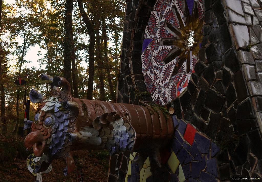 Incroyable gargouille brune et bleue, cherchant à s'échapper peut-être, surveillée par une rosace de bouteilles